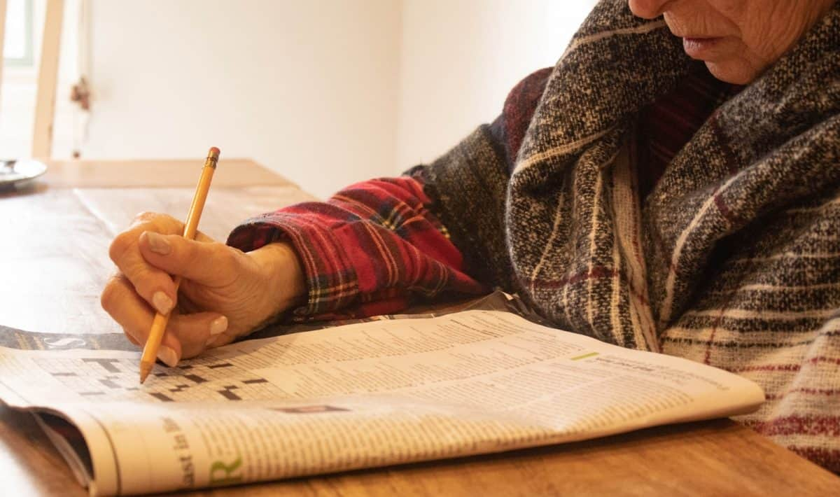 person in black and white sweater writing on white paper